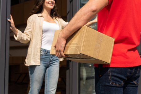 Photo for Selective focus of delivery man holding box near cheerful woman - Royalty Free Image