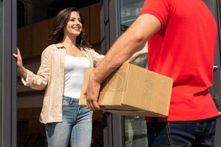 Photo pour Vue recadrée de l'homme de livraison retenant la boîte près de la femme gaie - image libre de droit