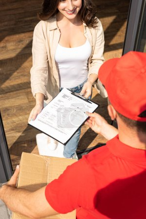 Photo for Overhead view of delivery man holding box and giving clipboard  to cheerful woman - Royalty Free Image
