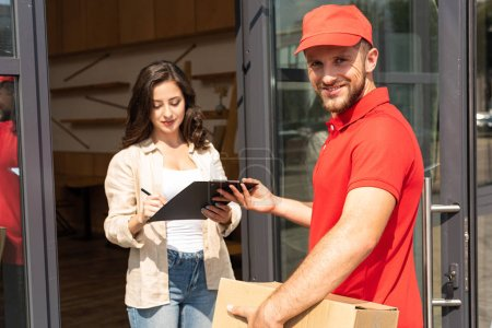 handsome delivery man holding clipboard near attractive girl