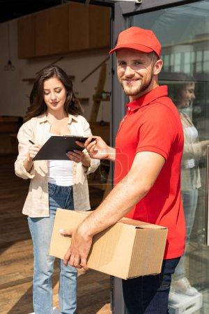 Photo pour Heureux livreur avec boîte tenant presse-papiers près de fille attrayante - image libre de droit