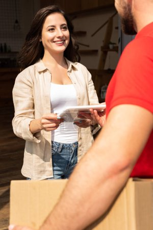 Photo for Selective focus of happy woman holding digital tablet and looking at delivery man with box - Royalty Free Image