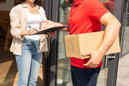 Photo pour Vue recadrée de livraison homme tenant boîte près de la fille avec presse-papiers - image libre de droit