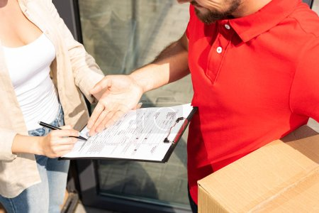 Photo for Cropped view of delivery man gesturing near clipboard in hands on woman - Royalty Free Image