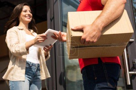 Photo pour Vue bas d'angle de l'homme de livraison donnant la tablette numérique à la fille heureuse - image libre de droit