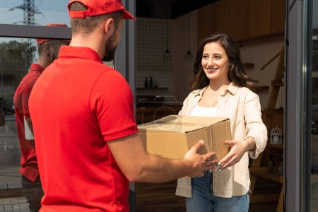 Photo for Delivery man giving cardboard box to happy woman - Royalty Free Image
