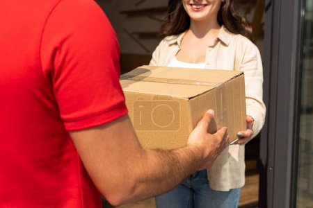 Photo for Cropped view of delivery man giving cardboard box to happy woman - Royalty Free Image