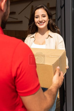 Photo for Cropped view of delivery man giving cardboard box to cheerful woman - Royalty Free Image