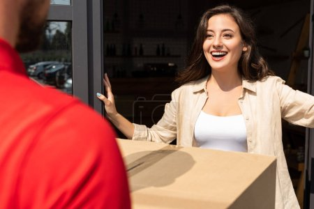 Photo for Selective focus of positive girl looking at delivery man with box - Royalty Free Image