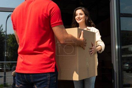 Photo pour Vue recadrée de l'homme de livraison donnant la boîte de carton à la jolie fille - image libre de droit