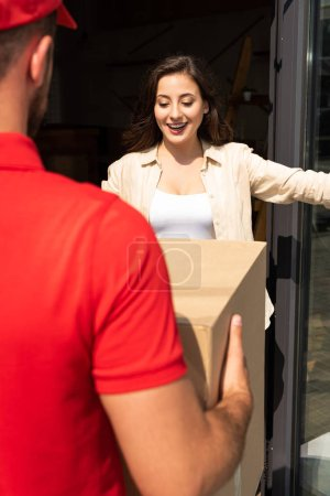 Photo for Cropped view of delivery man holding carton box near pretty girl - Royalty Free Image