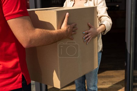 Photo for Cropped view of delivery man giving carton box to woman - Royalty Free Image