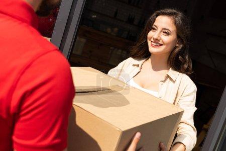 Photo pour Vue recadrée de livreur donnant la boîte de carton à la femme de sourire - image libre de droit