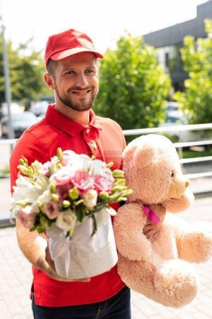 Foto de Enfoque selectivo de repartidor alegre sosteniendo oso de peluche y flores - Imagen libre de derechos