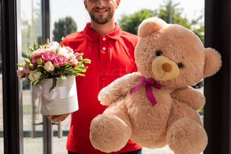 Photo pour Vue recadrée de l'homme de livraison positif retenant l'ours de nounours et les fleurs - image libre de droit