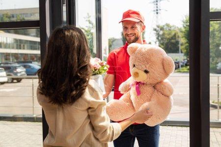 Foto de Enfoque selectivo del repartidor feliz en la gorra sosteniendo oso de peluche y flores cerca de la mujer - Imagen libre de derechos