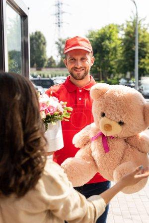 Foto de Enfoque selectivo del repartidor alegre en la gorra sosteniendo oso de peluche y flores cerca de la mujer - Imagen libre de derechos