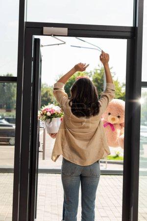 Foto de Vista trasera de la mujer de pie con las manos por encima de la cabeza cerca del repartidor con regalos - Imagen libre de derechos