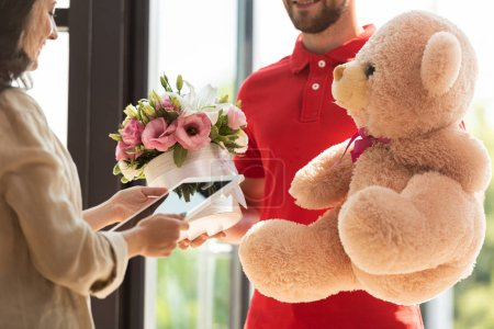Photo for Cropped view of happy delivery man holding teddy bear and flowers near girl with digital tablet - Royalty Free Image