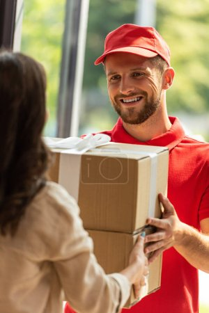 cropped view of woman receiving carton box from delivery man