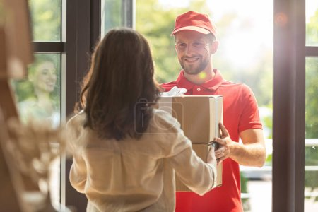 Photo for Back view of woman receiving carton box from happy delivery man - Royalty Free Image