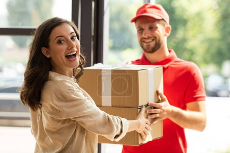 Photo for Selective focus of happy woman receiving carton boxes from cheerful delivery man in cap - Royalty Free Image