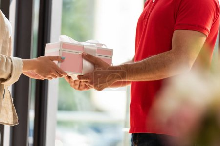 Photo for Cropped view of delivery man giving pink present to woman - Royalty Free Image