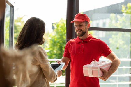 Photo for Selective focus of happy delivery man holding pink present and giving digital tablet to woman - Royalty Free Image