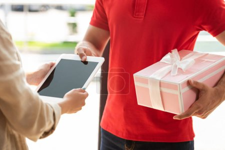Photo pour Vue recadrée du livreur tenant le cadeau rose et donnant la tablette numérique à la femme - image libre de droit