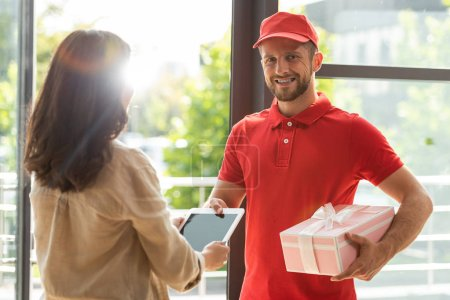 Photo for Happy bearded delivery man holding pink present near woman with digital tablet - Royalty Free Image