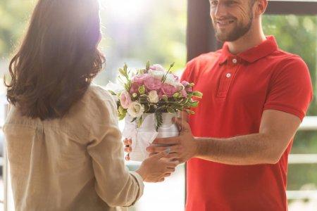 Photo pour Vue recadrée de livraison heureuse homme donnant des fleurs à la femme - image libre de droit