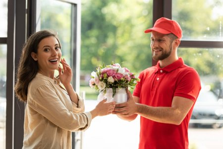 Photo pour Homme barbu et heureux de livraison donnant des fleurs à la belle femme - image libre de droit