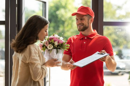 Photo for Bearded and happy delivery man holding clipboard near beautiful woman smelling flowers - Royalty Free Image