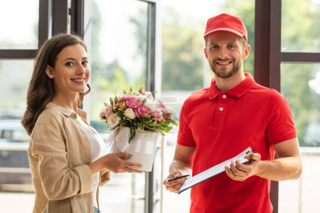 Photo for Bearded and cheerful delivery man holding clipboard near beautiful woman - Royalty Free Image