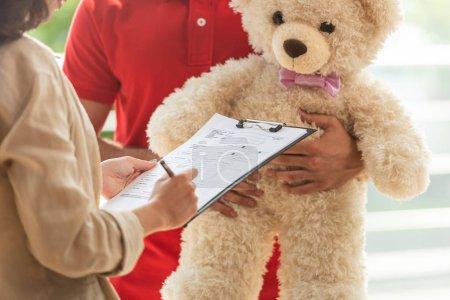 Photo pour Vue recadrée de papier de signature de fille sur le bloc-papiers près de l'homme avec l'ours de nounours - image libre de droit