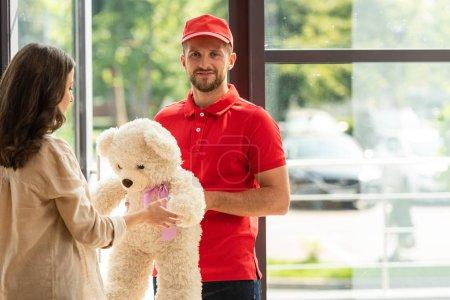 Foto de Hombre barbudo feliz en la gorra dando oso de peluche a la mujer - Imagen libre de derechos