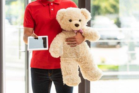 Photo pour Vue recadrée du livreur tenant un jouet doux et une tablette numérique - image libre de droit