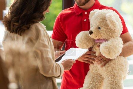 Photo pour Vue recadrée de femme retenant la tablette numérique près de l'homme avec l'ours de nounours - image libre de droit