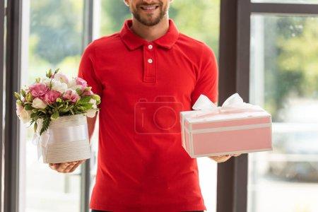 Photo pour Vue recadrée de l'homme barbu gai retenant des fleurs et la boîte rose de cadeau - image libre de droit