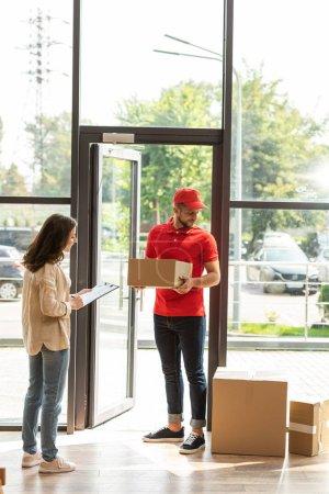 Photo pour Femme signature papier sur presse-papiers près de livraison homme et boîtes - image libre de droit