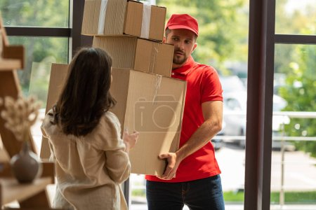 Photo for Selective focus of handsome delivery man holding carton boxes near woman at home - Royalty Free Image
