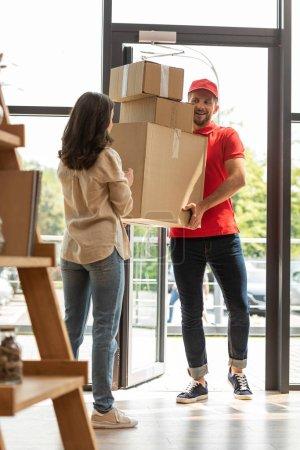 Foto de Enfoque selectivo de guapo repartidor sosteniendo cajas de cartón cerca de la niña en casa - Imagen libre de derechos