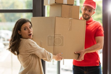 Photo for Selective focus of surprised girl taking carton boxes near delivery man - Royalty Free Image
