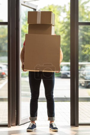 Photo for Delivery man covering face while standing and holding carton boxes - Royalty Free Image