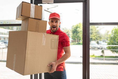 surprised and bearded man holding carton boxes while looking at camera