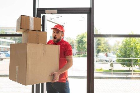 Photo pour Homme choqué et barbu tenant des boîtes en carton tout en regardant la caméra - image libre de droit