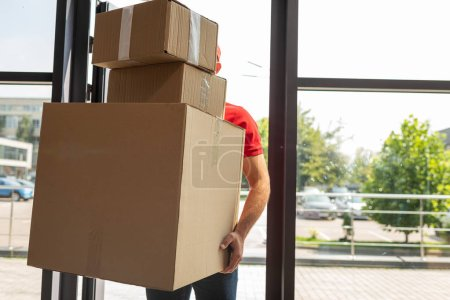 Photo for Delivery man covering face while holding carton boxes - Royalty Free Image