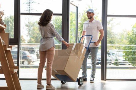Photo for Handsome delivery man holding delivery cart with boxes near woman - Royalty Free Image