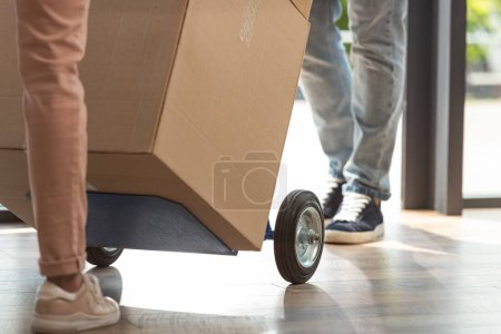 Photo for Cropped view of delivery man holding delivery cart with box near girl - Royalty Free Image