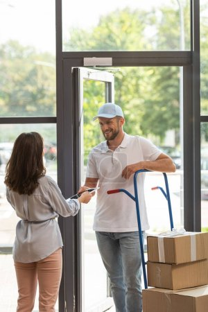 Photo for Happy delivery man standing near delivery cart with boxes and woman with digital tablet - Royalty Free Image